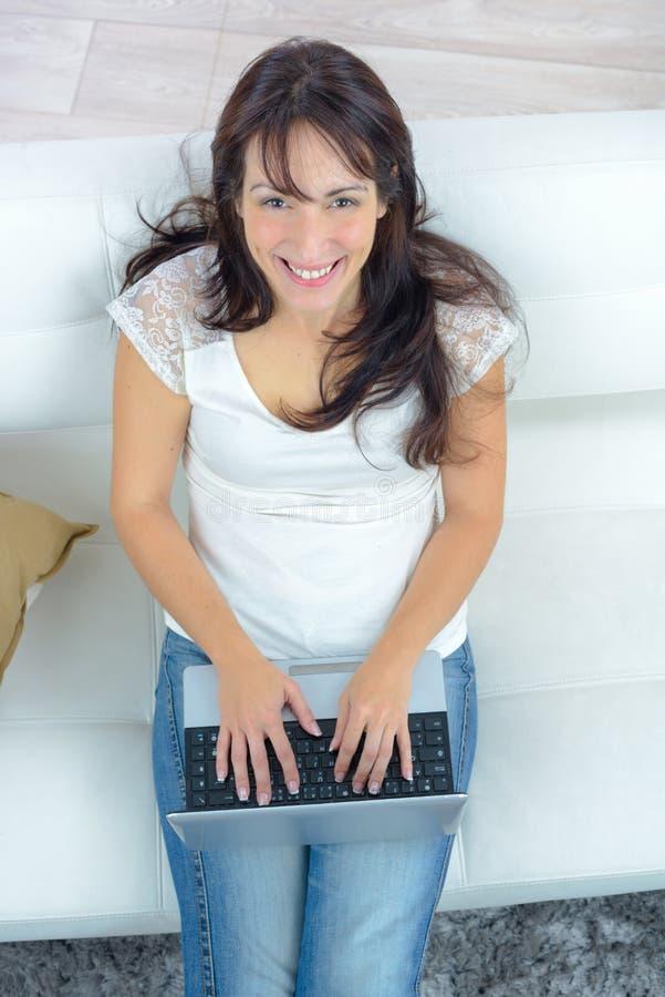 Szczęśliwa kobieta pracuje na laptopie - widok od above obraz royalty free