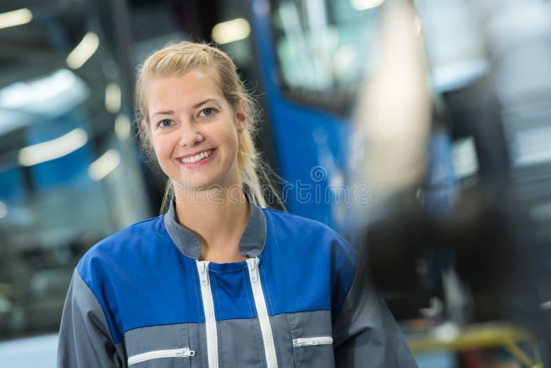 Szczęśliwa kobieta pracuje w samochodowym warsztacie indoors obrazy royalty free