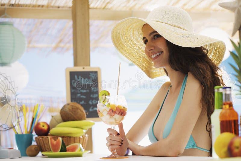 Szczęśliwa kobieta przy plażowym łasowaniem owocowa sałatka zdjęcia royalty free