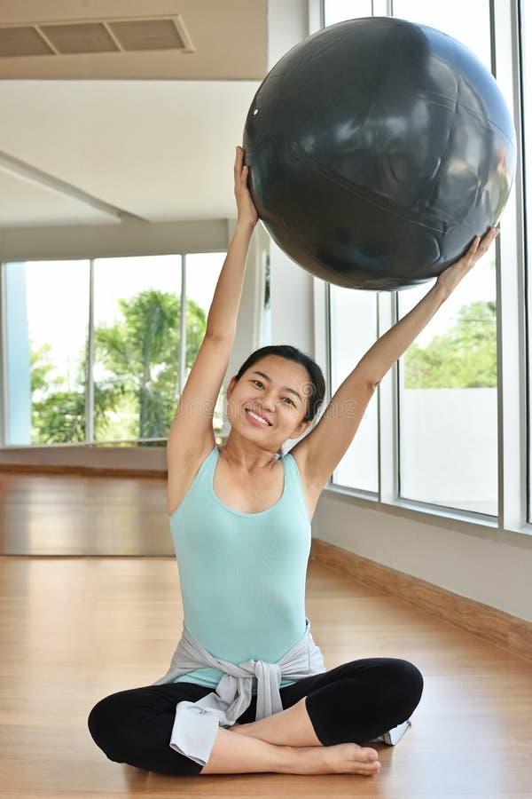 Szczęśliwa kobieta robi ćwiczeniom z sprawności fizycznej piłką fotografia royalty free