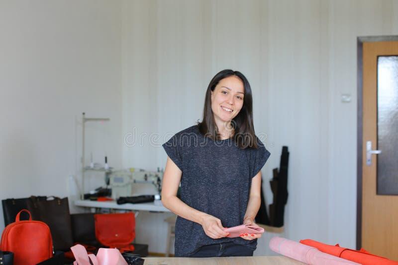 Szczęśliwa kobieta robi różowemu rzemiennemu portfla atelier w domu obraz stock