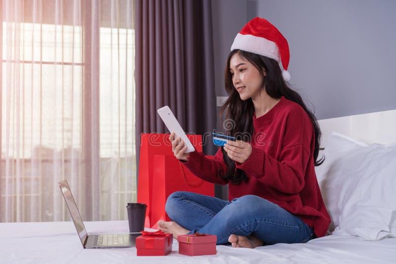 Szczęśliwa kobieta robi zakupy online dla Bożenarodzeniowego prezenta z cyfrowym tabl obraz royalty free