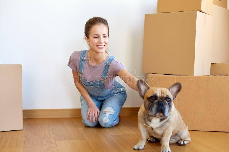 Szczęśliwa kobieta rusza się nowy dom z psem i pudełkami zdjęcia stock