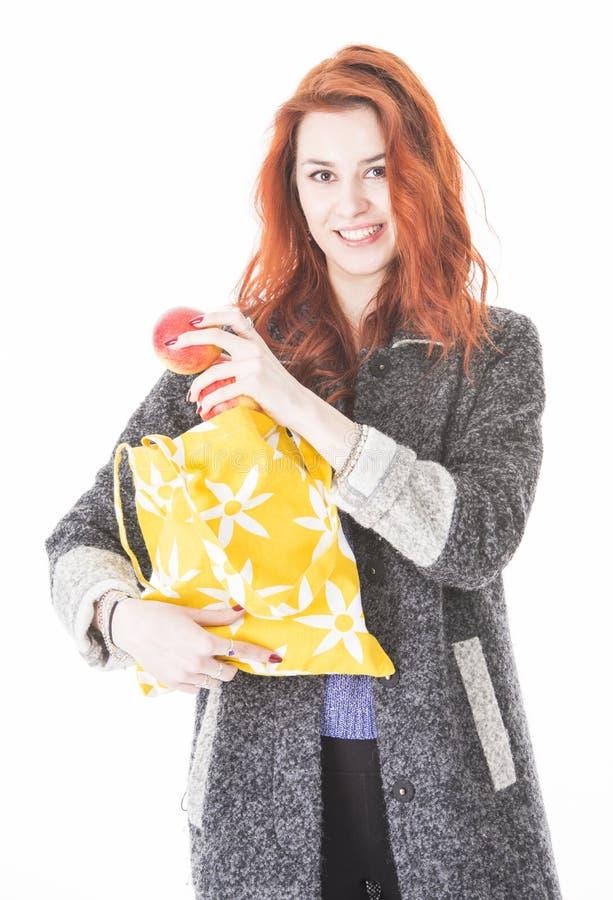 Szczęśliwa kobieta stawia owoc w eco życzliwej sukiennej torbie obraz royalty free