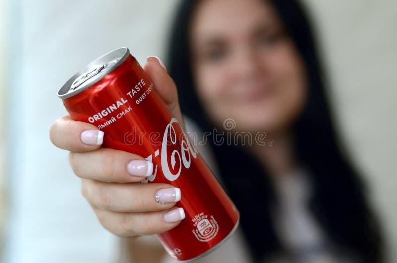 Szczęśliwa kobieta trzyma bezalkoholowego koka-kola aluminiową blaszaną puszkę w garażu wnętrzu zdjęcie royalty free
