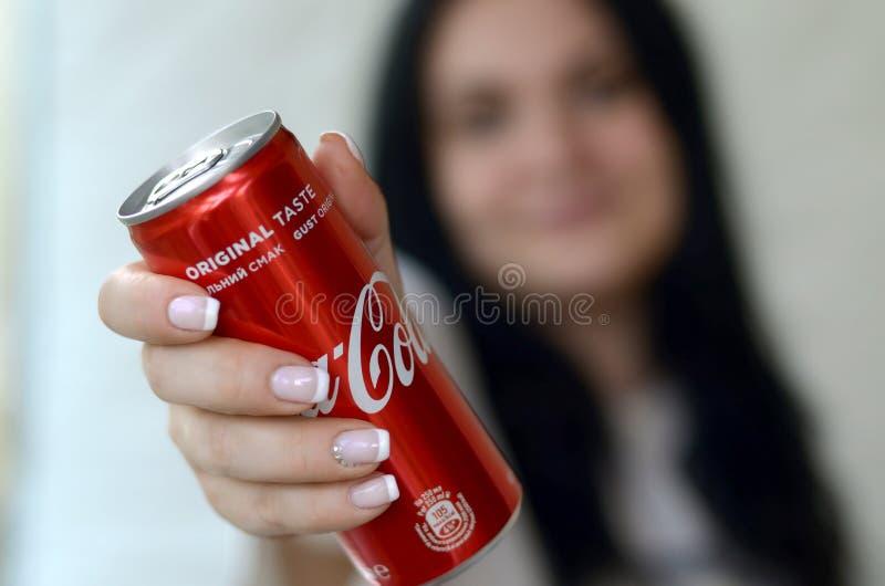 Szczęśliwa kobieta trzyma bezalkoholowego koka-kola aluminiową blaszaną puszkę w garażu wnętrzu obraz stock
