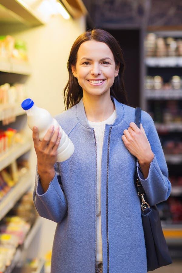 Szczęśliwa kobieta trzyma dojną butelkę w rynku zdjęcie stock