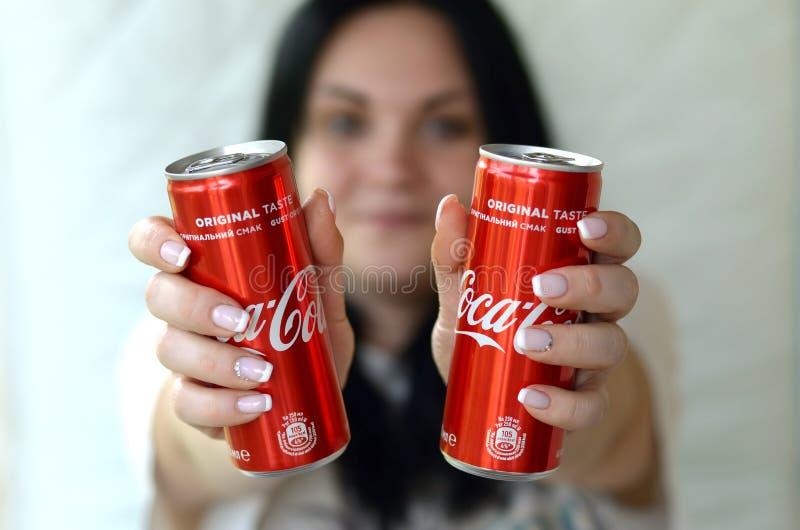 Szczęśliwa kobieta trzyma dwa bezalkoholowego koka-kola aluminiowej blaszanej puszki w garażu wnętrzu zdjęcie royalty free