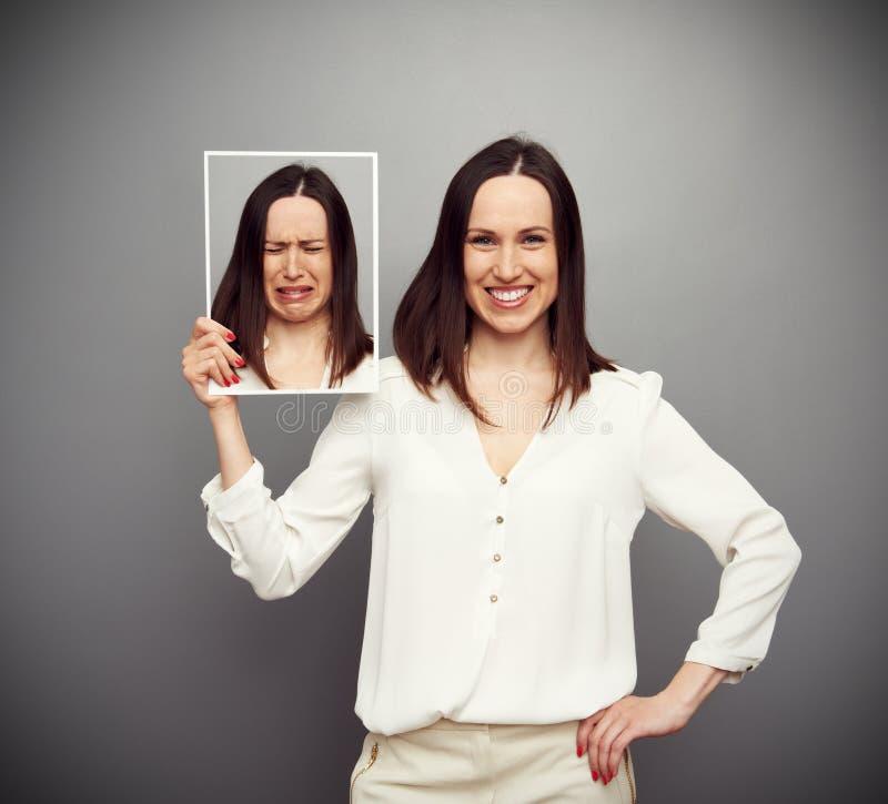 Szczęśliwa kobieta trzyma jej smutnego obrazek obrazy stock