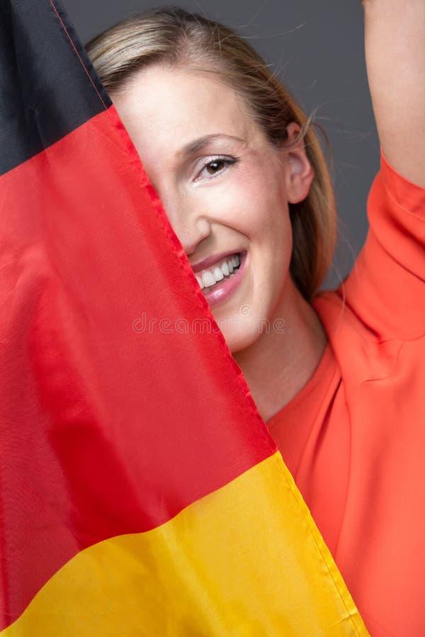 Szczęśliwa kobieta trzyma Niemiecką flaga obraz royalty free