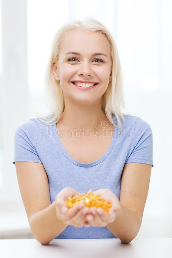 Szczęśliwa kobieta trzyma rybiego oleju kapsuły w domu obrazy stock