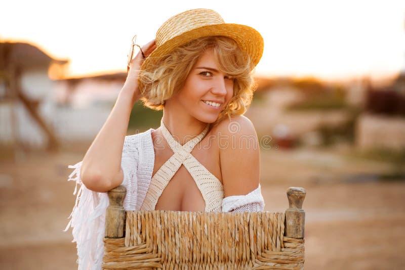 Szczęśliwa kobieta uśmiecha się plażowego kapelusz ma lato zabawę podczas wakacji i jest ubranym być na wakacjach, plenerowy obraz royalty free