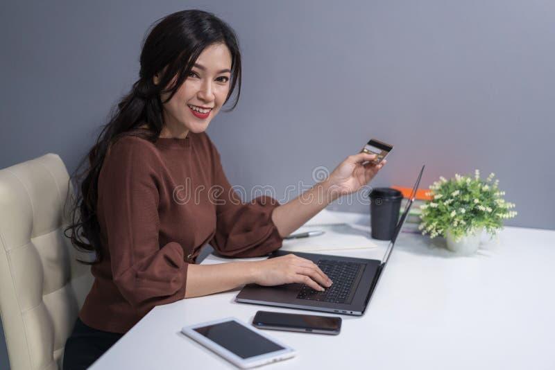 Szczęśliwa kobieta używa laptop dla online zakupy z credi zdjęcia stock