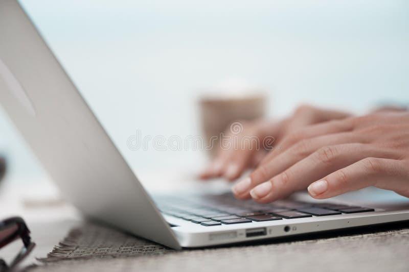 Szczęśliwa kobieta używa laptop przy kawiarnią blisko lily farbuje miękki na widok wody zdjęcia stock