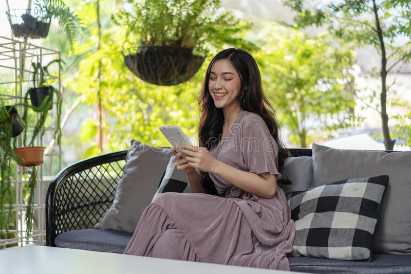 Szczęśliwa kobieta używa pastylkę w café fotografia royalty free