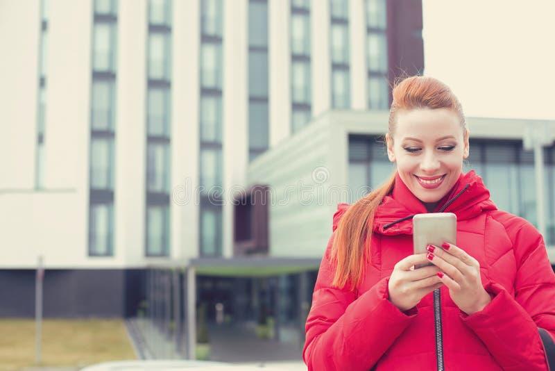 Szczęśliwa kobieta używa texting na mądrze telefonie outdoors na miasta tle zdjęcie royalty free