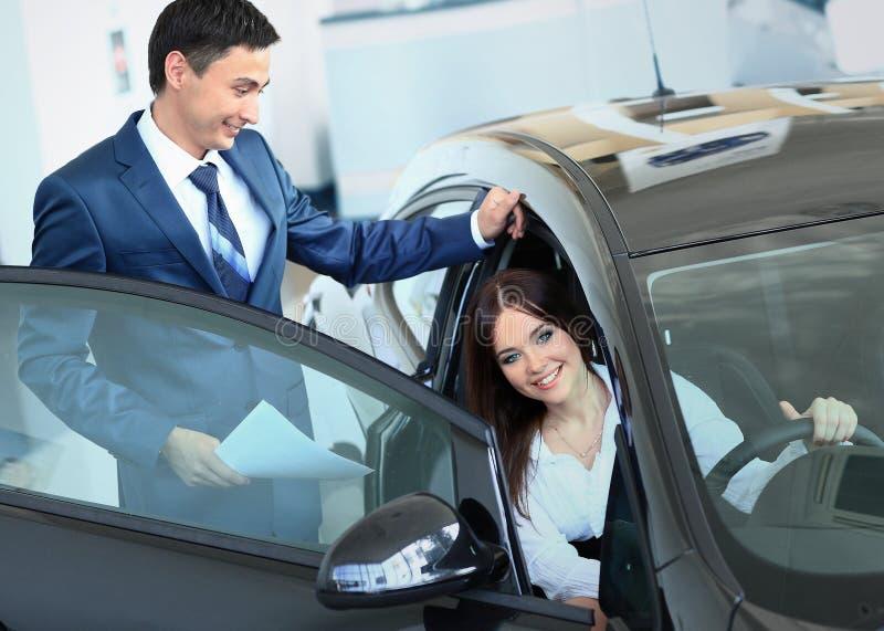 Szczęśliwa kobieta wśrodku samochodu w auto przedstawieniu lub salonie zdjęcia stock