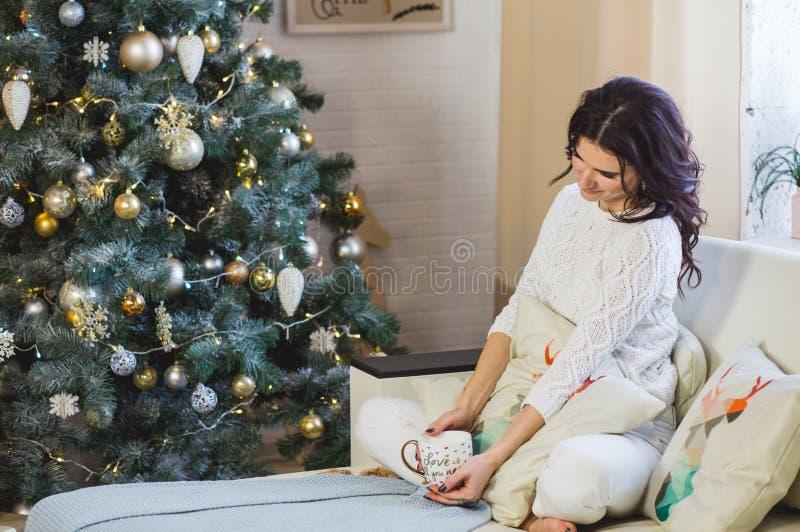 Szczęśliwa kobieta w biel dziam być ubranym relaksuje w domu dla bożych narodzeń fotografia stock