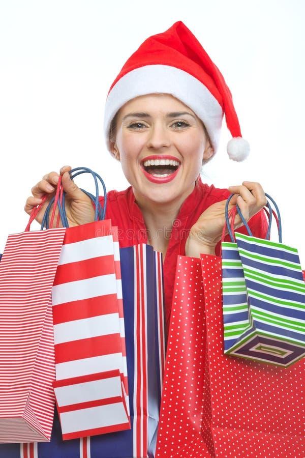 Szczęśliwa kobieta w Bożenarodzeniowym kapeluszu z torba na zakupy zdjęcia stock