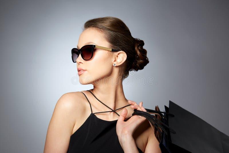 Szczęśliwa kobieta w czarnych okularach przeciwsłonecznych z torba na zakupy zdjęcie royalty free