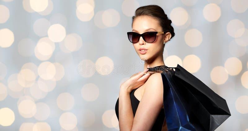 Szczęśliwa kobieta w czarnych okularach przeciwsłonecznych z torba na zakupy zdjęcia royalty free