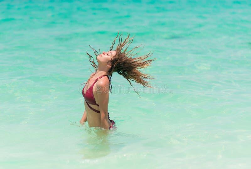 Szczęśliwa kobieta w czerwonym bikini jest bawić się i bryzgająca w morzu fotografia royalty free