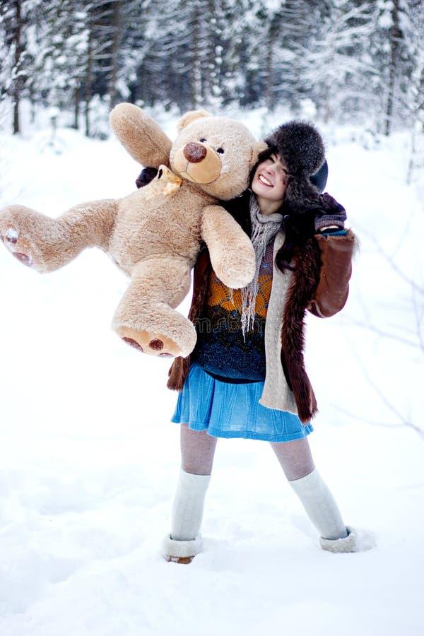 Szczęśliwa kobieta w futerkowym żakiecie z niedźwiedziem na białym śnieżnym zimy tle i ushanka zdjęcie stock