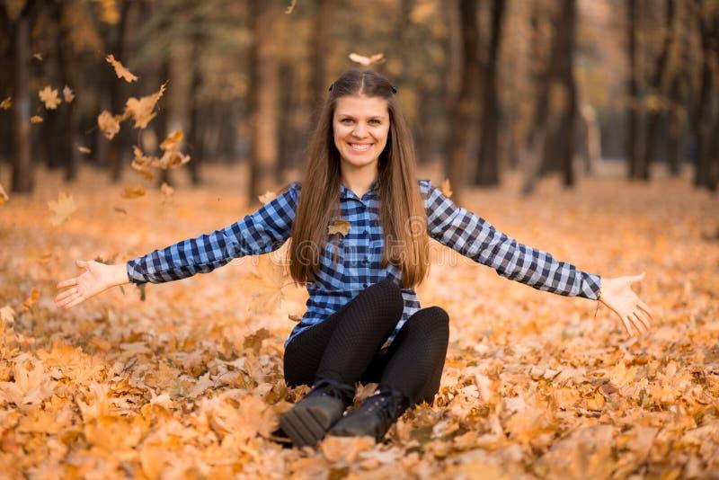 Szczęśliwa kobieta w jesieni radośnie ciska w górę żółtych liści szczęście w małych rzeczach zdjęcie stock