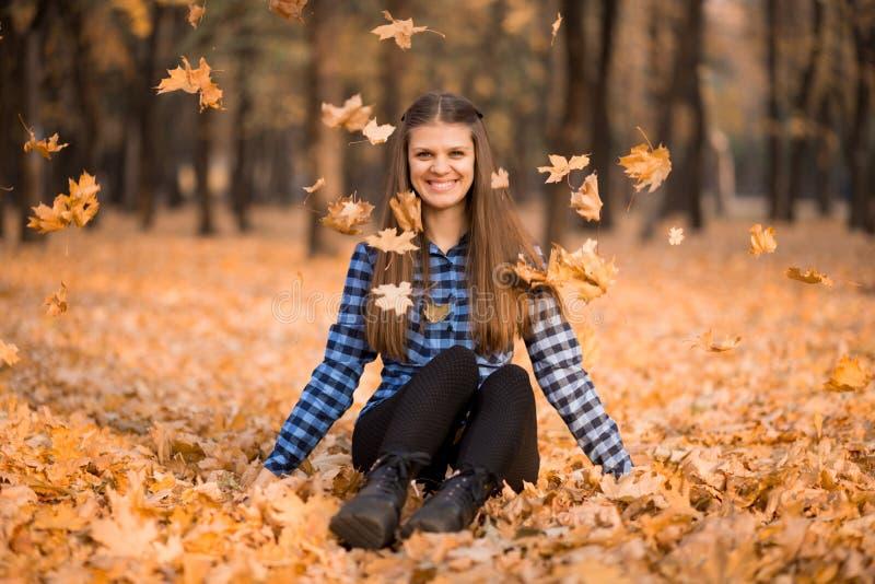 Szczęśliwa kobieta w jesieni siedzi na trawie i radośnie ciska w górę żółtych liści obrazy stock