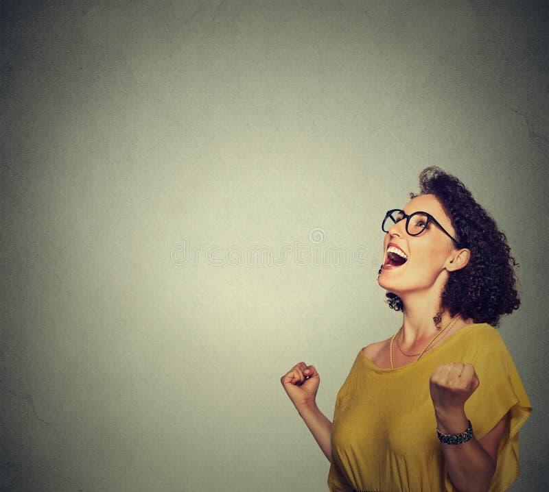 Szczęśliwa kobieta w kolor żółty sukni exults pompujący pięści ekstatyczne świętuje sukces obrazy royalty free