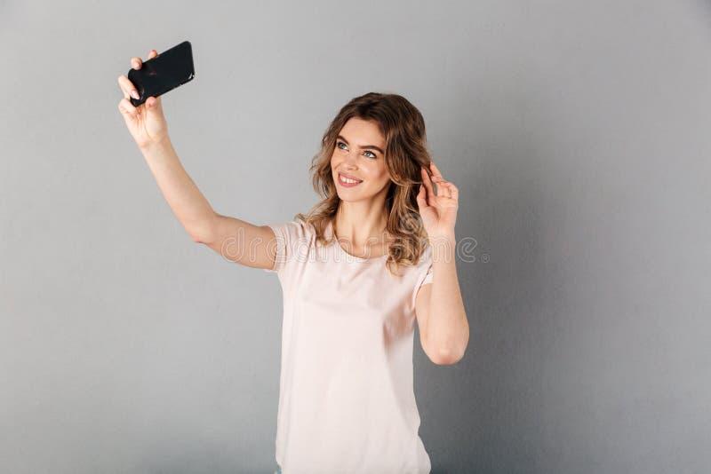Szczęśliwa kobieta w koszulce robi selfie na smartphone zdjęcie royalty free