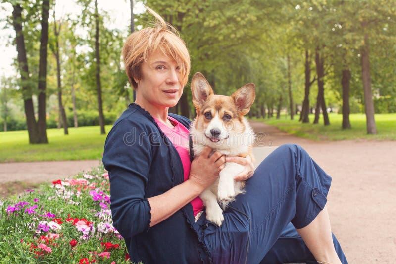 Szczęśliwa kobieta w ogródzie z jej psim corgi obraz royalty free