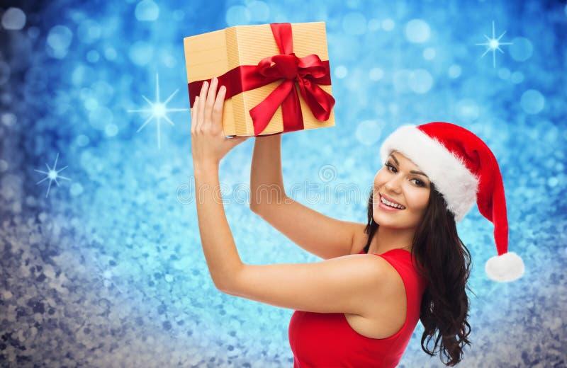 Szczęśliwa kobieta w Santa kapeluszu z prezentem nad błyskotliwością zdjęcia royalty free