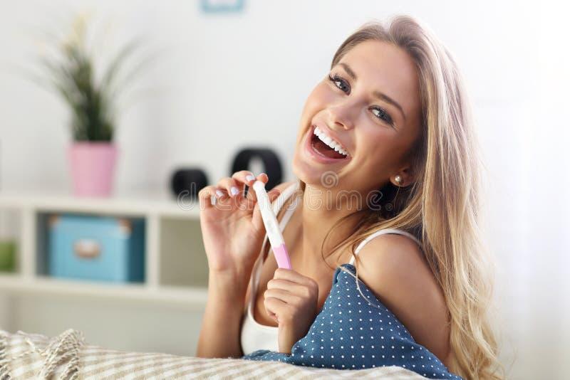 Szczęśliwa kobieta z ciążowym testem w domu fotografia stock