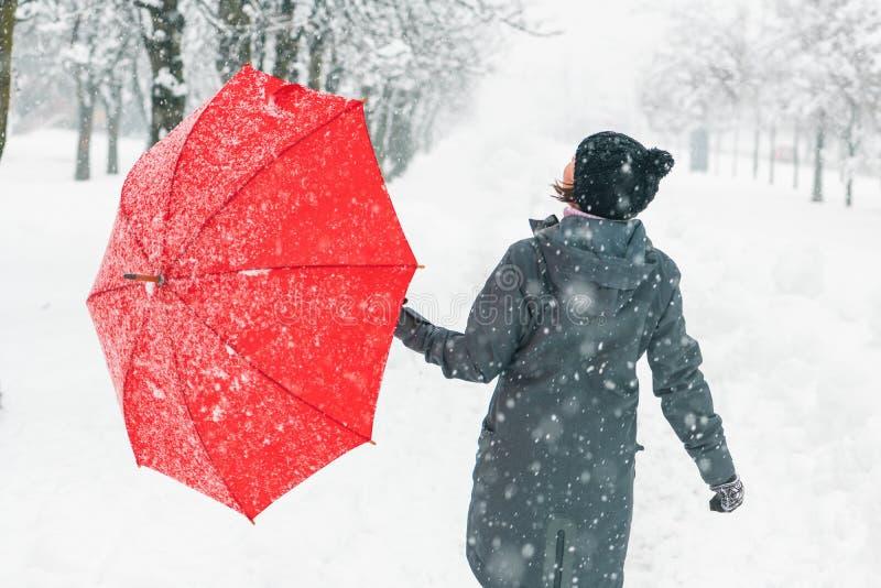 Szczęśliwa kobieta z czerwonym parasolowym cieszy się zima śniegiem zdjęcia royalty free