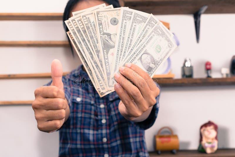 Szczęśliwa kobieta z dolarowymi rachunkami pokazuje kciuk up zdjęcia stock