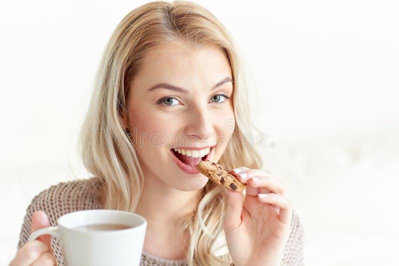 Szczęśliwa kobieta z herbacianym łasowania ciastkiem w domu zdjęcie stock