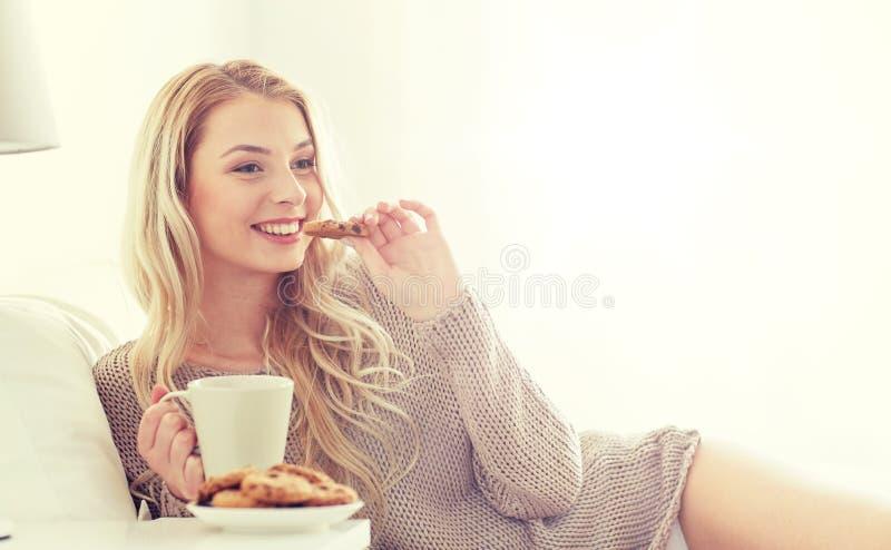 Szczęśliwa kobieta z kawą i ciastkami w łóżku w domu zdjęcie royalty free