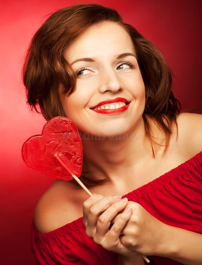 Szczęśliwa kobieta z kierowym cukierku lolly wystrzałem zdjęcia royalty free