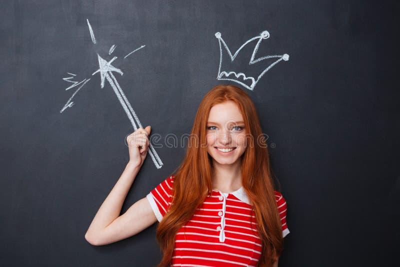Szczęśliwa kobieta z koroną i magia rysująca na blackboard tle fotografia royalty free