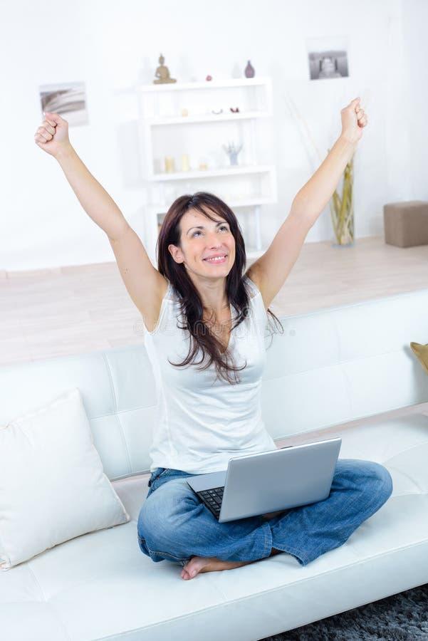 Szczęśliwa kobieta z laptopem i kredytową kartą robi online zakupy zdjęcie stock