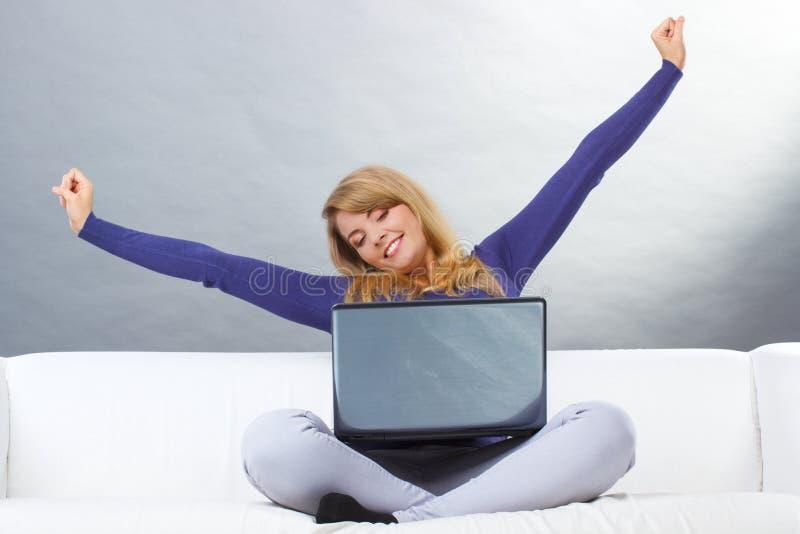 Szczęśliwa kobieta z laptopu obsiadaniem na kanapie i rozciąganiu ona ręki zdjęcia royalty free