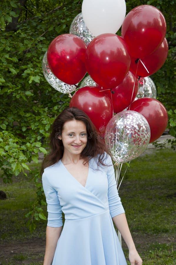 Szczęśliwa kobieta z baloonami urodzinowymi na zewnątrz latem Gotowy do ucieczki zdjęcia stock