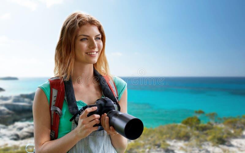Szczęśliwa kobieta z plecakiem i kamerą nad seashore zdjęcie stock