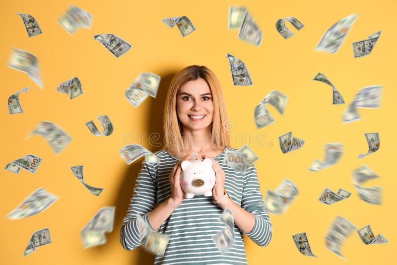 Szczęśliwa kobieta z prosiątko bankiem i latanie pieniądze obraz stock