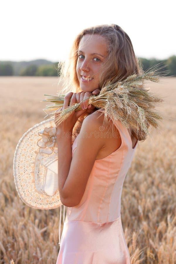 Szczęśliwa kobieta z pszenicznymi ucho i kapeluszem w jej rękach zdjęcie stock