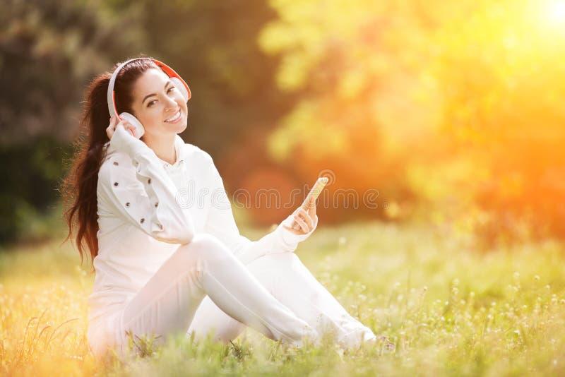 Szczęśliwa kobieta z rozluźniającymi się słuchawkami w jesiennym parku Piękna natura z kolorowym tłem Kobieta moda cieszy się zdjęcie royalty free