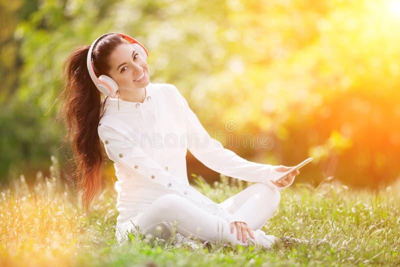Szczęśliwa kobieta z rozluźniającymi się słuchawkami w jesiennym parku Piękna natura z kolorowym tłem Kobieta moda cieszy się obraz royalty free