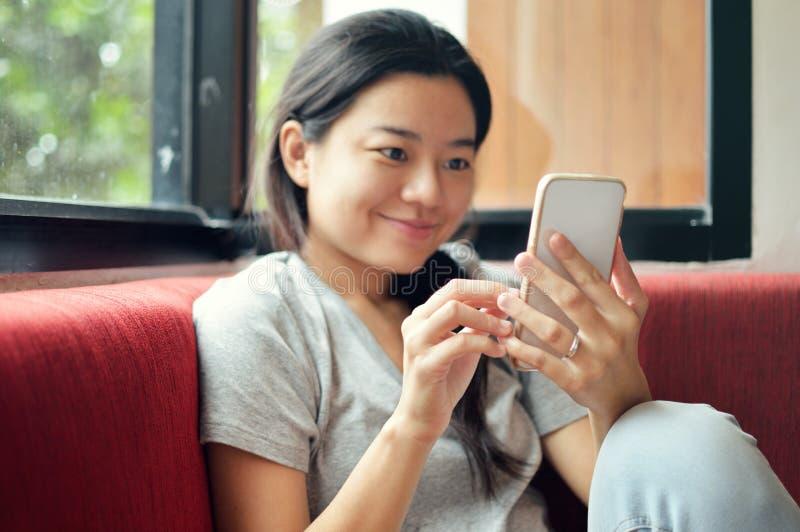 Szczęśliwa kobieta z smartphone macaniem parawanowym i używa app fotografia royalty free