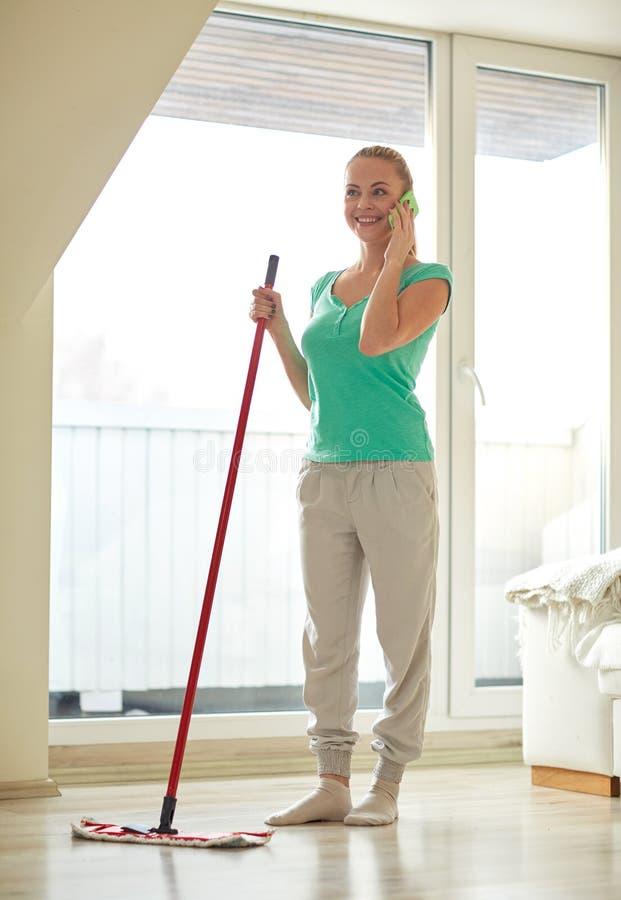 Szczęśliwa kobieta z smartphone mopping podłoga w domu obrazy stock